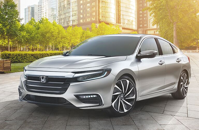 2019 Honda Insight exterior front shot of grille, fascia, and turning wheel parked on a tile road in the middle of a forest park