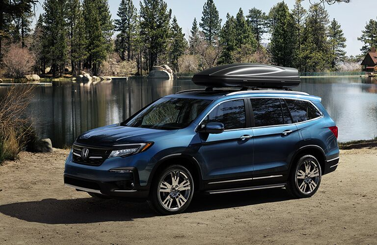 2019 Honda Pilot exterior side shot blue paint job parked on a beach next to a lake within a forest