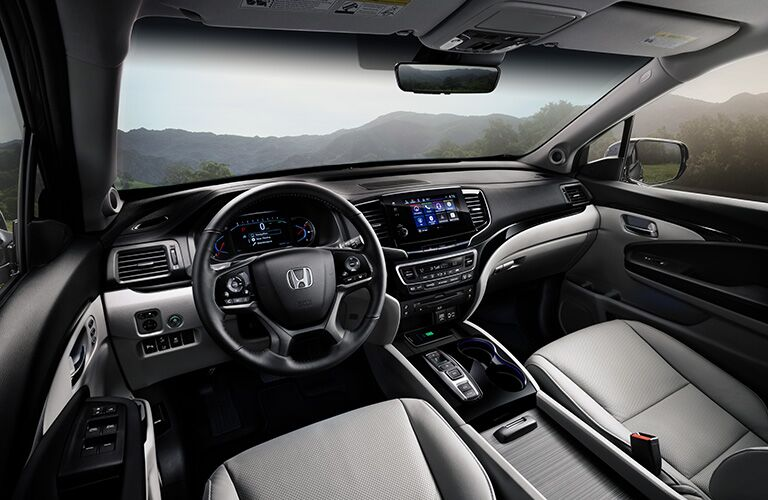2019 Honda Pilot interior shot of front seating, steering wheel, transmission, and dashboard screens