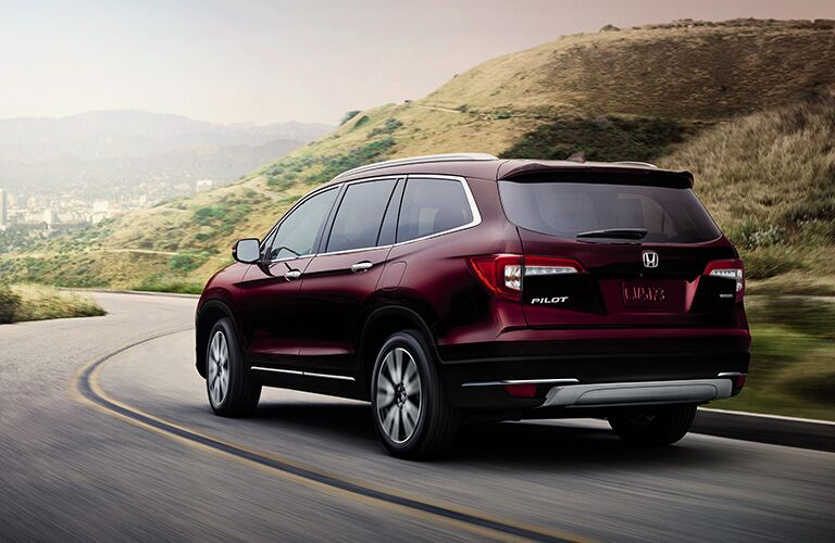2019 Honda Pilot exterior shot rear red paint job driving on a winding country highway road