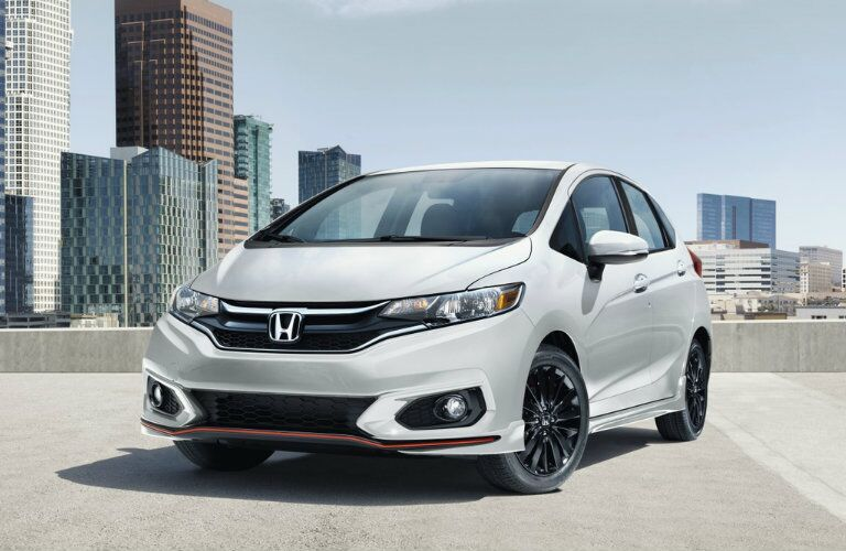 2019 Honda Fit exterior shot gray paint color parked on the roof of a building with a cityscape background