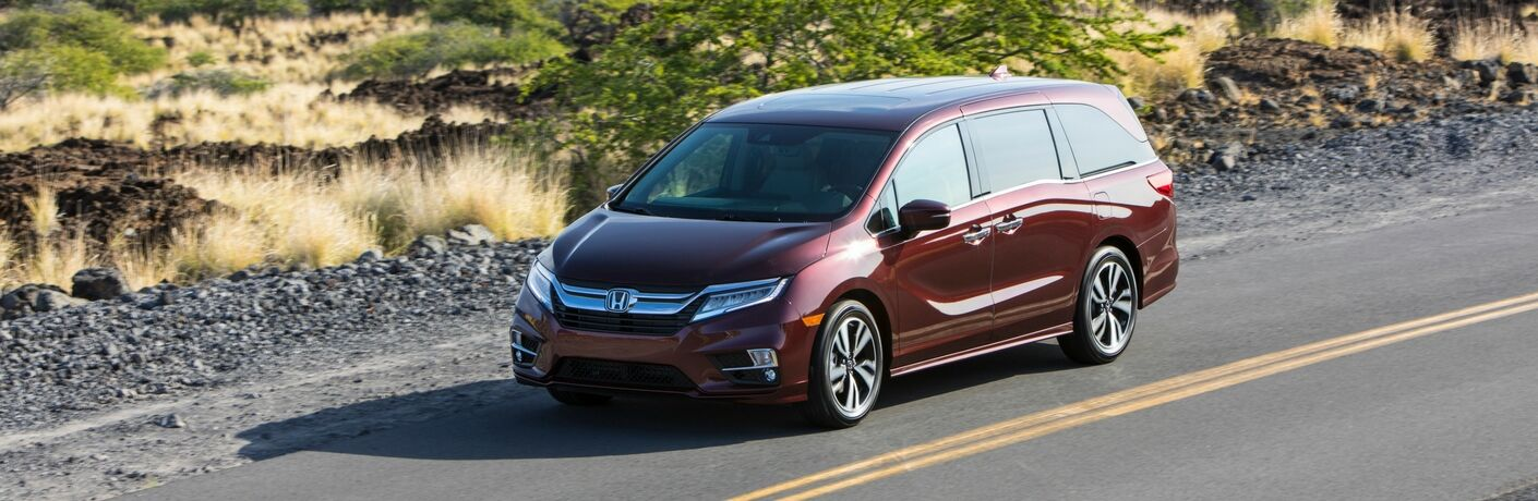 2019 Honda Odyssey red exterior shot driving down a country road next to fields of grass on the highway