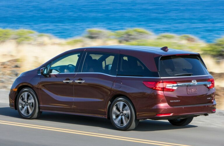 2019 Honda Odyssey red exterior shot driving on a highway next to a grassy beach and the sea