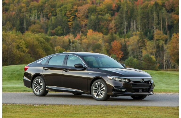 2019 Honda Accord Hybrid exterior side shot parked on a asphalt road near grass hills and a forest