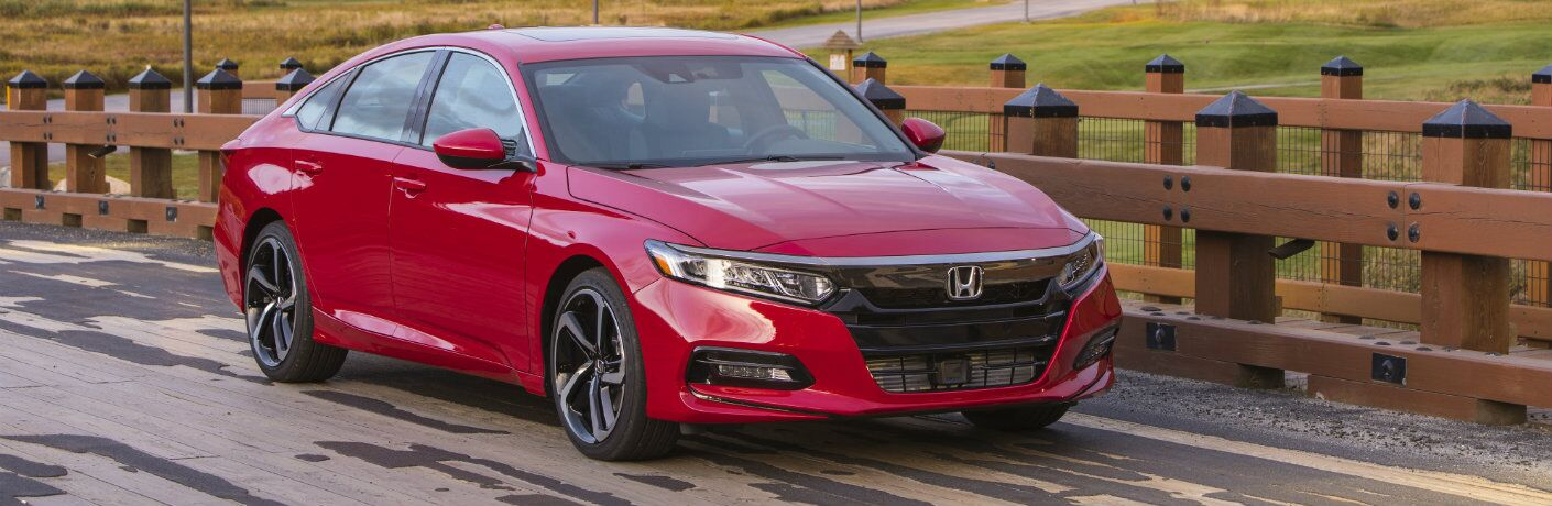 2019 Honda Accord Spot exterior shot with red paint color parked next to a fence with a forest, castle, and mountains behind it