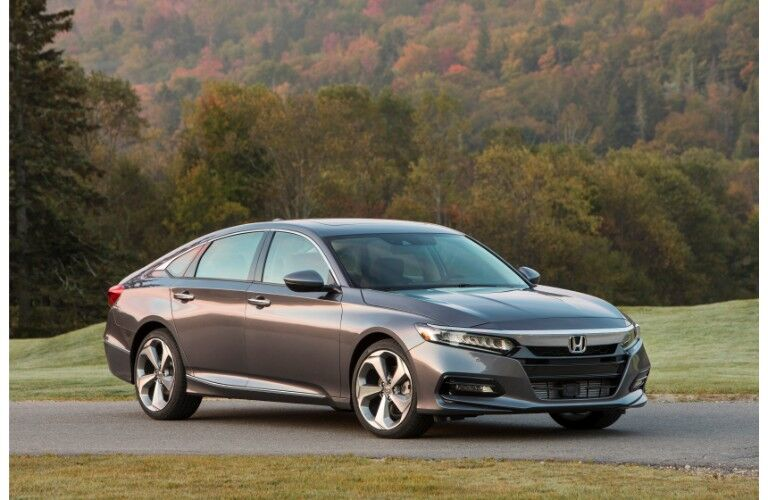 2019 Honda Accord Touring exteriror shot with dark gray paint color parked on an asphalt walking path near a forest