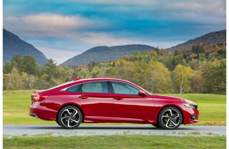 2019 Honda Accord sport exterior side shot with red paint color parked in a grass field with forest hills behind it