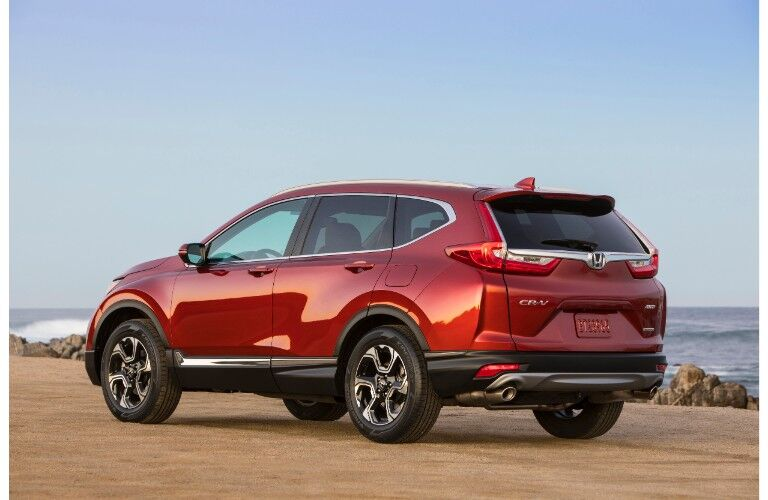 2019 Honda CR-V exterior rear shot with molten lava pearl paint color parked on a wet beach near rocks and ocean waves