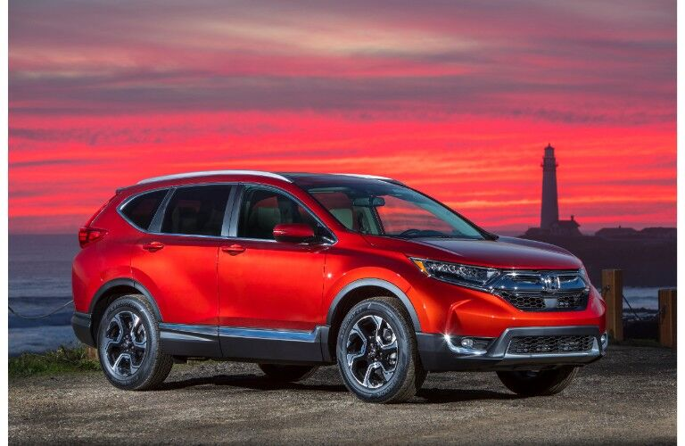 2019 Honda CR-V exterior side shot with molten lava pearl paint color parked on a pier with a red sunset sky and a lighthouse behind it