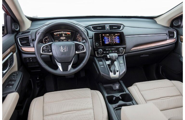 2019 Honda CR-V interior shot of front seating view, steering wheel with Honda logo badge, transmission knob, and dashboard display layout