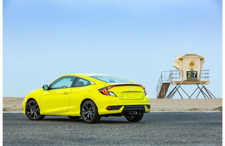 2019 Honda Civic Coupe exterior rear shot with tonic yellow pearl paint color parked near a beach and lifeguard station