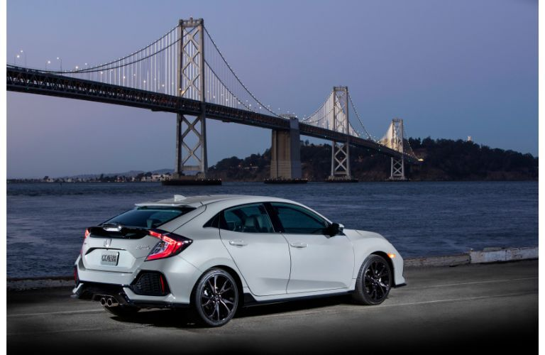 2019 Honda Civic Hatchback exterior shot at night with gray paint color with a long gray bridge in the background