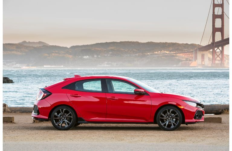 2019 Honda Civic Hatchback exterior side shot with red paint color parked near the sea and the golden gate bridge