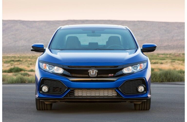 2019 Honda Civic Si sedan exterior front shot of headlights and grille with a grassy hill behind it