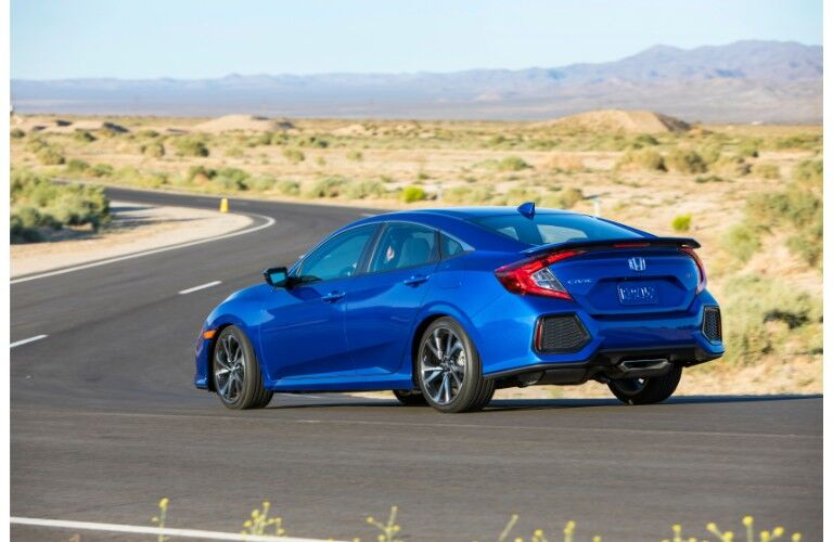 2019 Honda Civic Si sedan exterior side shot with blue paint color parked on the side of a curving desert highway