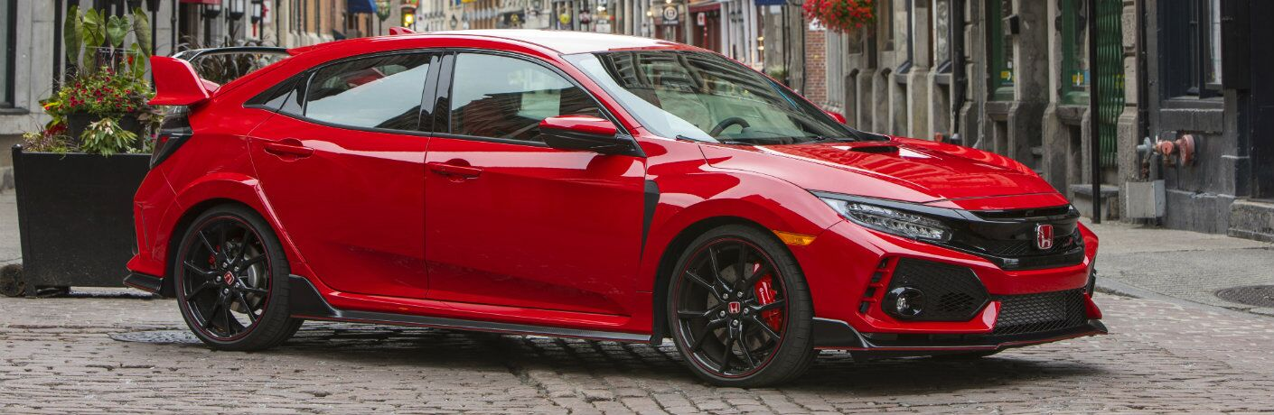 2019 Honda Civic Type R exterior side shot with rallye red paint color parked on a stone tile street in a European city