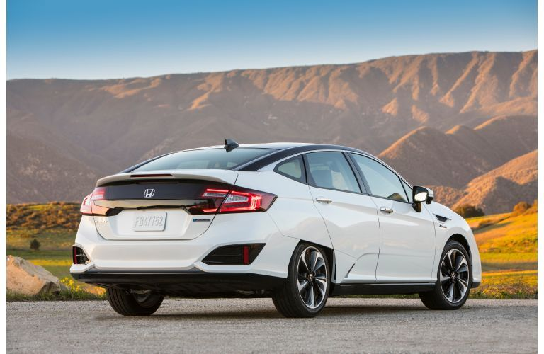 2019 Honda Clarity Fuel Cell exterior shot of back bumper, taillights, and trunk with white paint color parked outside near large roaming hills