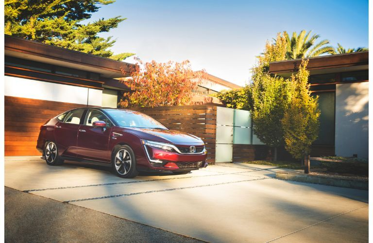 2019 Honda Clarity Fuel Cell exterior shot with dark red paint color parked on a driveway outside the garage of a luxury home