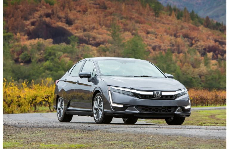 2019 Honda Clarity Plug-In Hybrid exterior front shot with gray paint color parked outside a forest hill