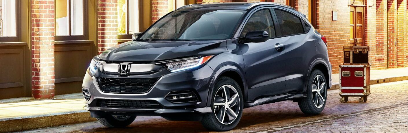 2019 Honda HR-V exterior shot parked on a brick-tiled road next to luggage and a brick windowed building