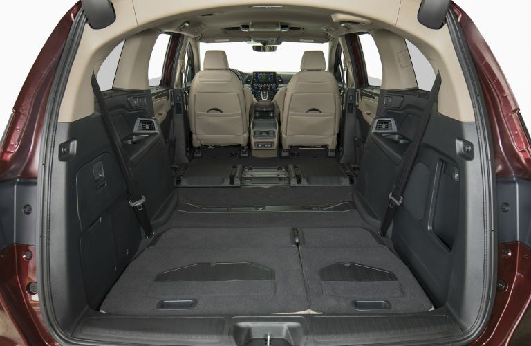 2019 Honda Odyssey interior view of power tailgate open and folded down magic slide seats to show maximum cargo capacity room in the trunk