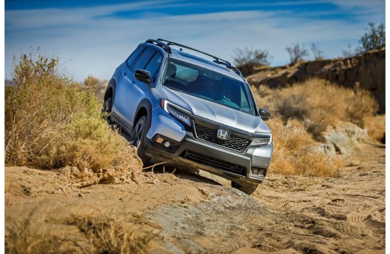 2019 Honda Passport exterior shot with gray silver paint color driving in a barren rocky wilderness off road over bumpy terrain