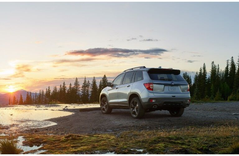 2019 Honda Passport exterior shot with silver paint color parked on a gravel beach by a lake and forest at sunset