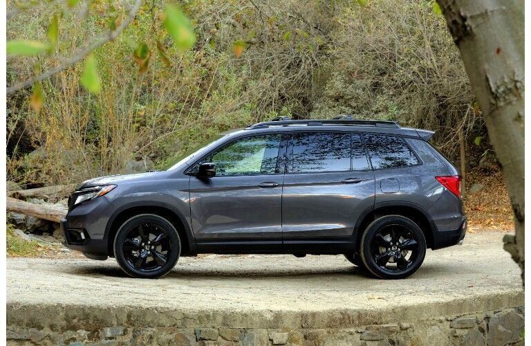 2019 Honda Passport exterior side shot with dark gray paint color parked on a rocky platform with green brush in the background