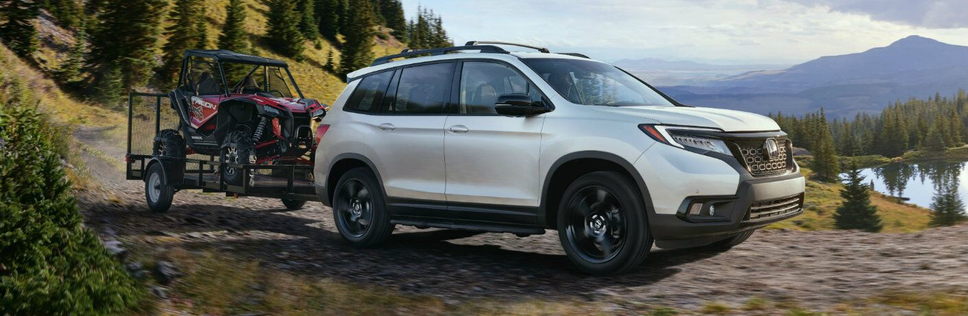 2019 Honda Passport exterior side shot with white paint color towing an off-road buggy down a hill near forests and lakes