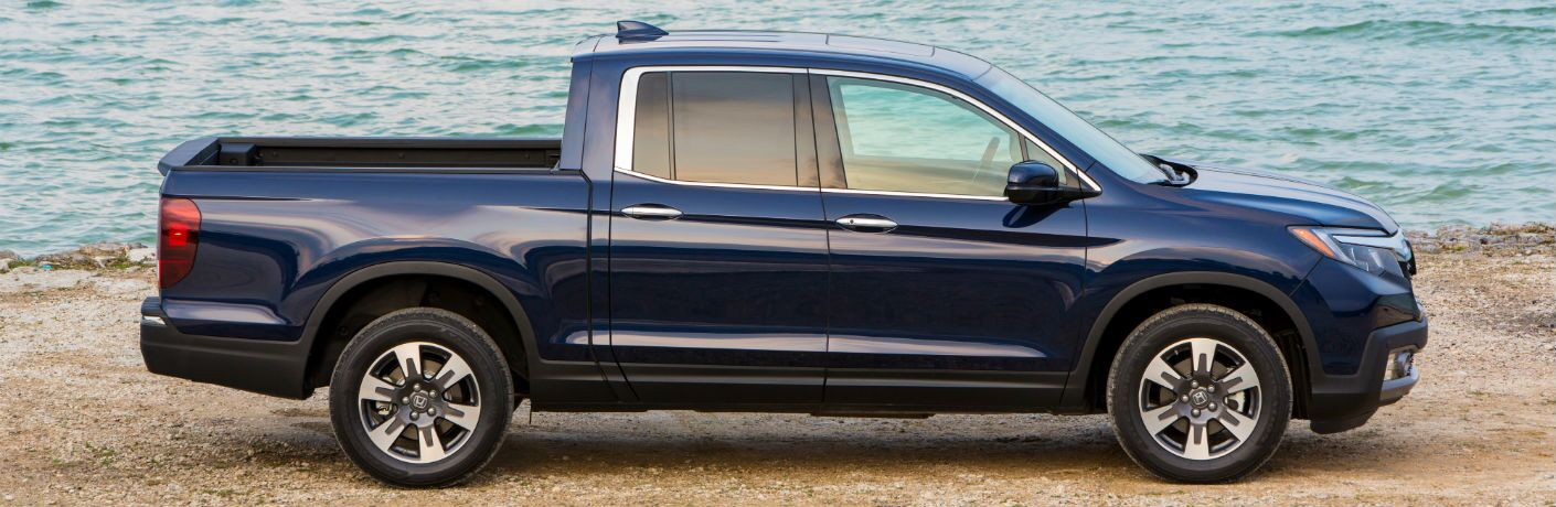 2019 Honda Ridgeline exterior side blue paint parked on a sandy beach near the tide of the sea
