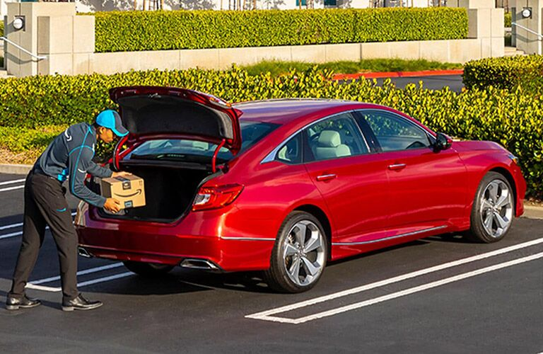 Man Putting a Package in the Trunk of a Red 2021 Honda Accord