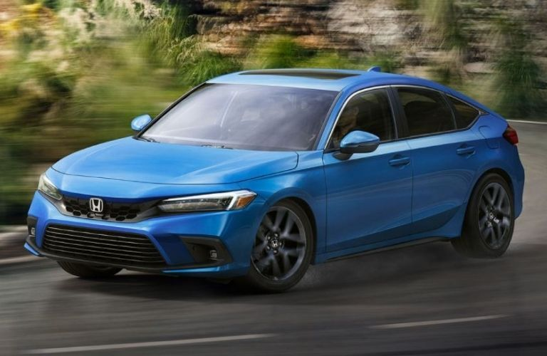Front view of a blue 2022 Honda Civic Hatchback cornering a road