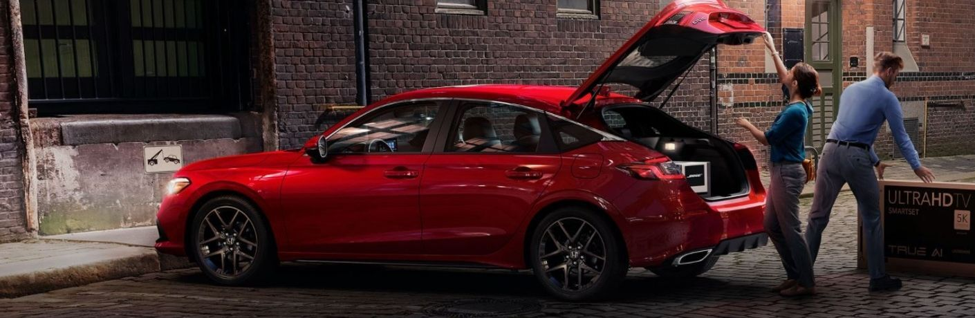 A man and a woman loading cargo in a red 2022 Honda Civic hatchback