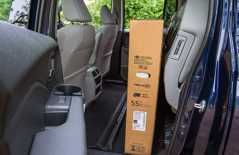fold-up back seats in 2018 honda ridgeline showed with large tv placed between them and front seats
