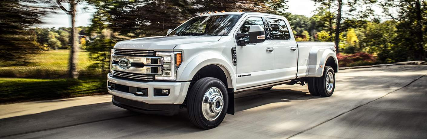 2018 Ford Super Duty Limited in white color dually driving down forest road