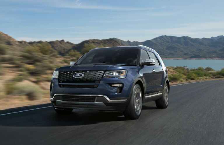 Exterior of 2018 Ford Explorer in blue driving on mountain road near Kingston, ON