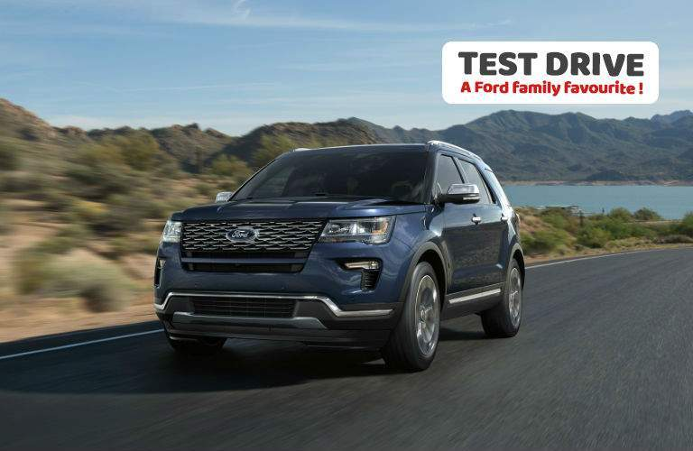 2018 ford explorer in blue driving with overlaid text to test drive a ford family favourite