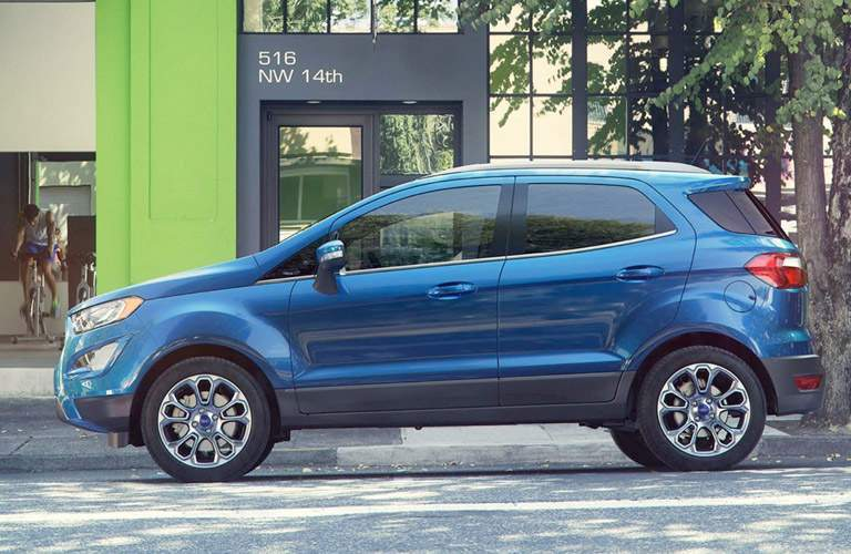 Side profile of the 2018 Ford EcoSport parked in front of a building with trees
