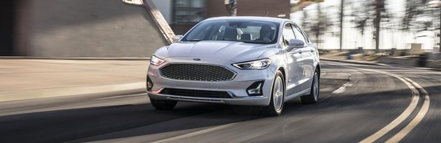 white 2019 ford fusion driving around corner on road