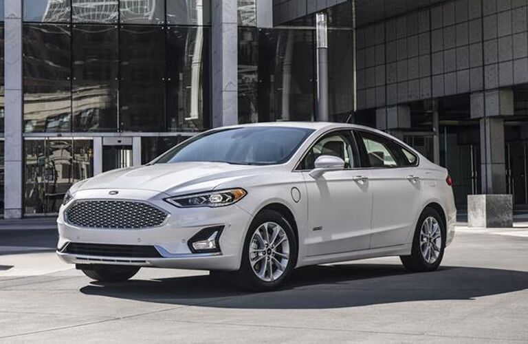 front and side view of white 2019 ford fusion parked in front of glass building