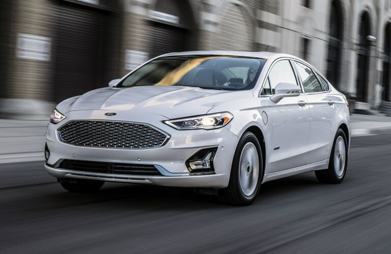 white 2019 ford fusion driving on city road