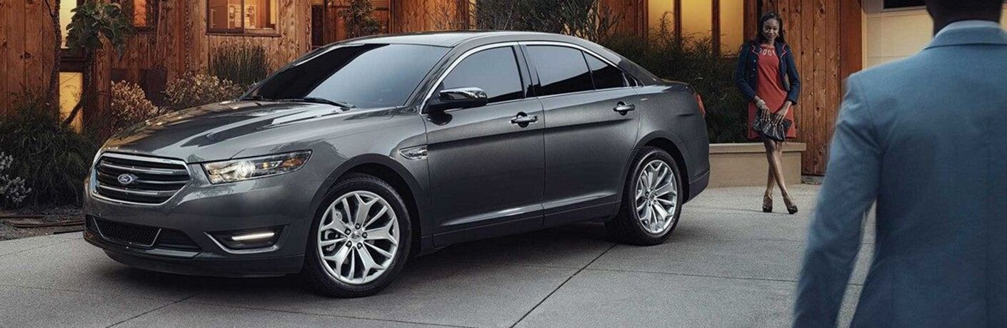 gray 2019 ford taurus in driveway of modern home