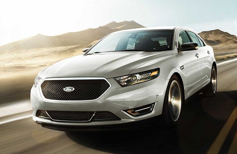 front view of white 2019 ford taurus driving on empty desert road
