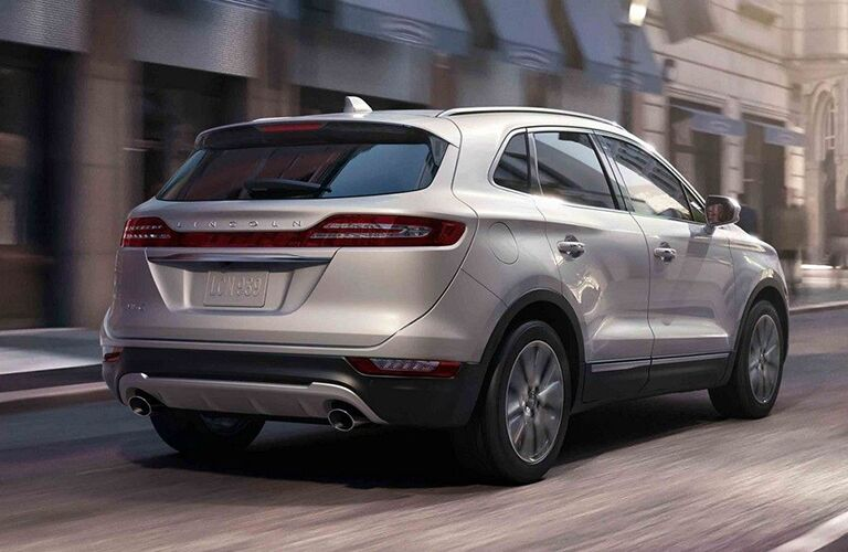 rear view of silver 2019 lincoln mkc driving past city buildings