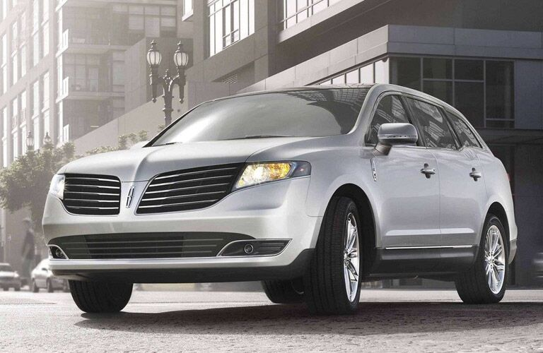 silver lincoln mkt parked on street by buildings
