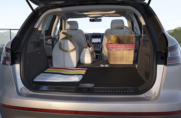rear cargo space of 2019 lincoln nautilus with seats folded down and luggage inside