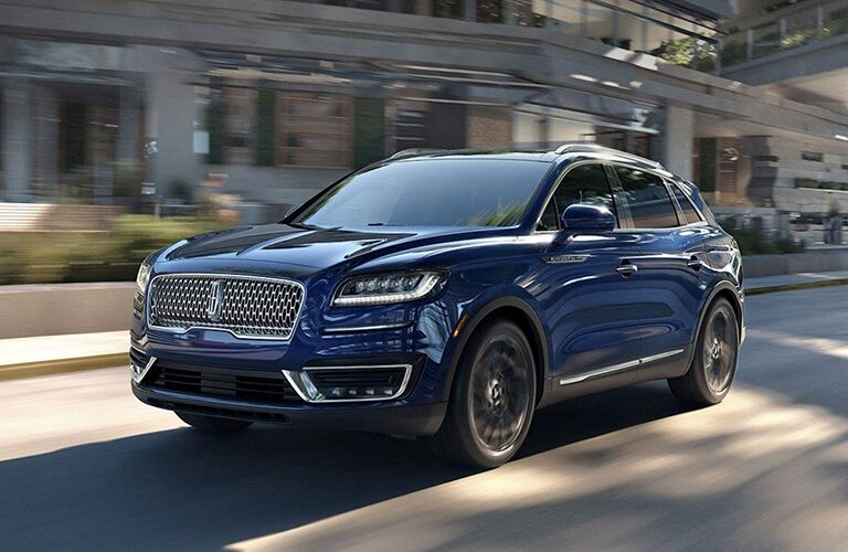 front and side view of blue 2019 lincoln nautilus driving on city street