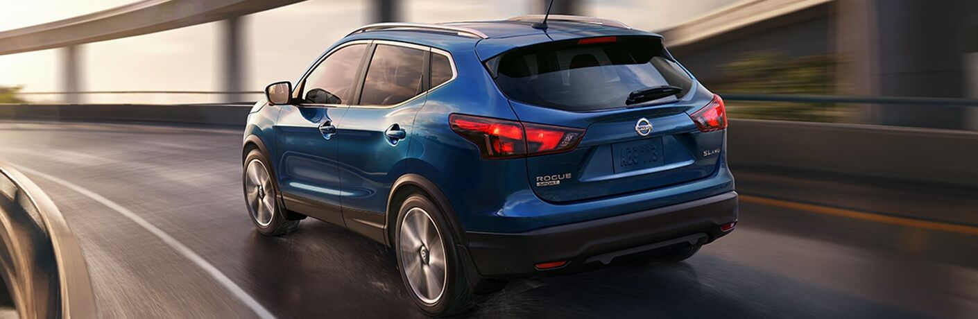 rear view of blue 2018 nissan rogue sport driving on highway