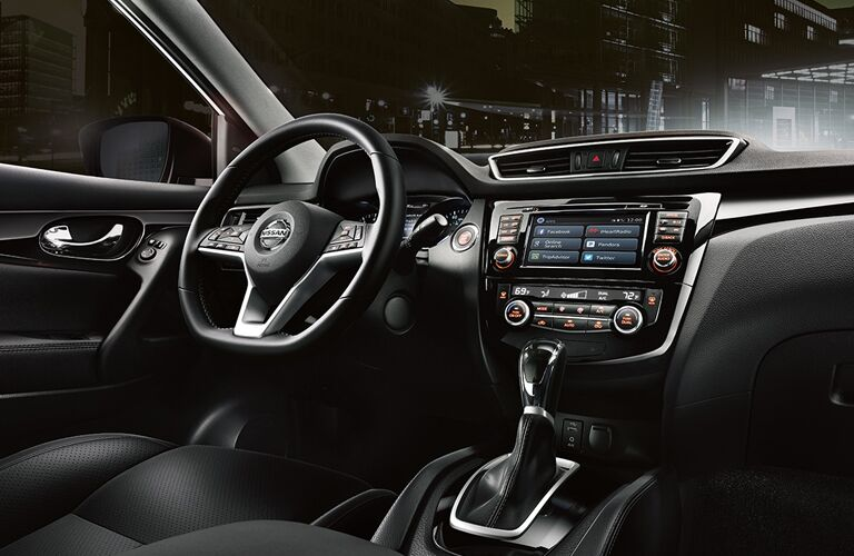 front interior of 2018 nissan rogue sport including steering wheel and infotainment system