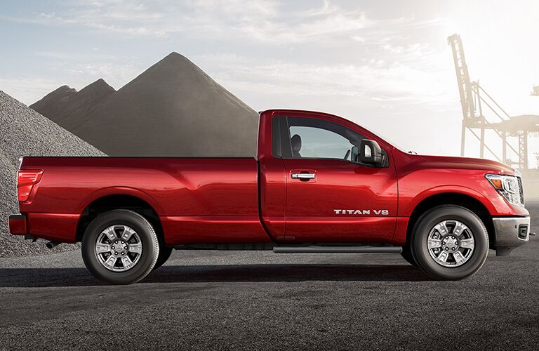 side view of red 2018 nissan titan next to gravel piles